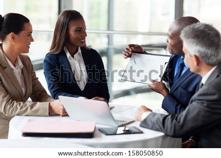 african businessman explaining sales graph to colleagues in meeting - stock photo