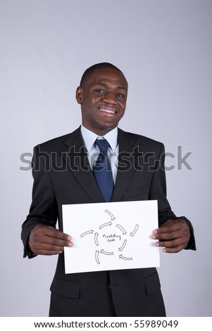 african businessman holding a marketing diagram solution - stock photo