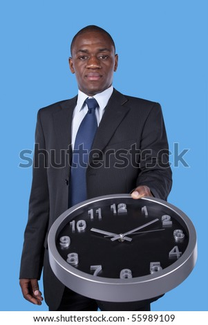 african businessman holding an office clock - stock photo