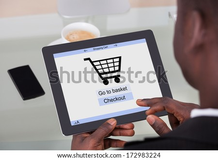 African Businessman Holding Digital Tablet With Online Shopping Application On A Screen - stock photo