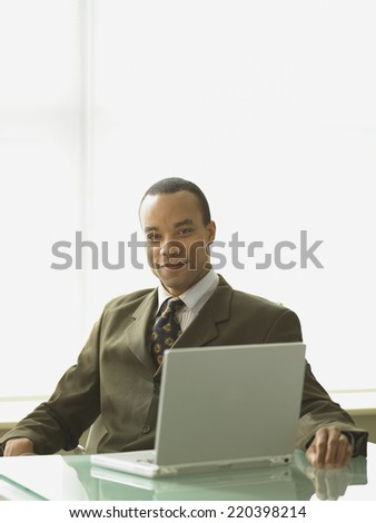 African businessman sitting at his desk with a laptop - stock photo