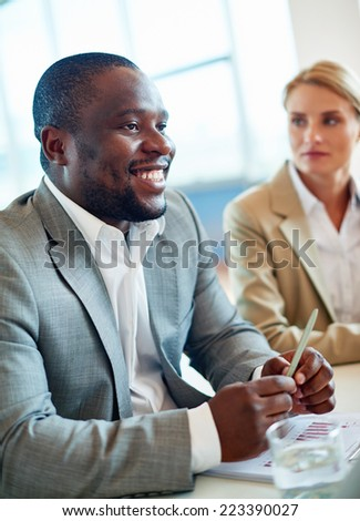 African businessman sitting at workplace in office on background of female colleague