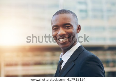 African businessman smiling confidently in city with sunflare - stock photo