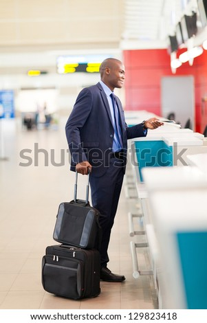 african businessman standing by airport check in counter - stock photo