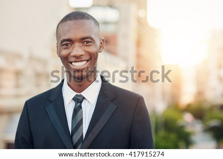 African businessman standing outside in a city smiling broadly - stock photo