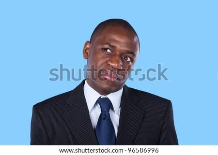 African businessman thinking (blue background) - stock photo