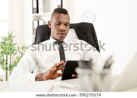 African businessman using digital tablet in office.