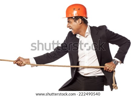 African businessman with a helmet pulling a rope - stock photo