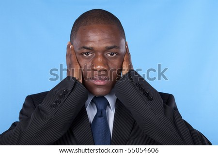 african businessman with hands covering his ears
