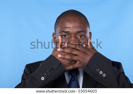 african businessman with hands covering his mouth