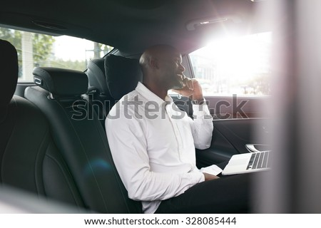 African businessman with laptop talking on mobile phone inside a car. Young entrepreneur working during travelling to office in a luxury car. - stock photo
