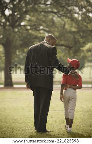 African businessman with son in baseball uniform - stock photo