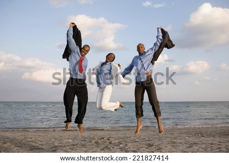 African businesspeople cheering at beach - stock photo