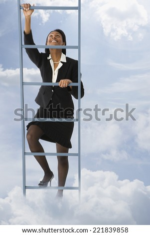 African businesswoman climbing ladder in clouds - stock photo
