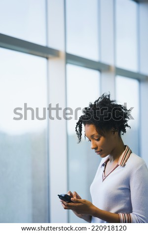 African businesswoman dialing cell phone - stock photo