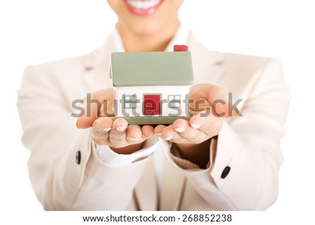 African businesswoman holding small house on palm. - stock photo