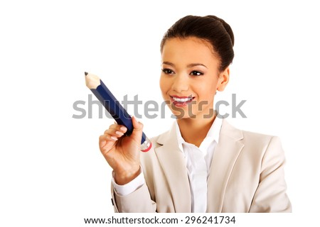 African businesswoman pointing with big pencil. - stock photo