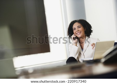 African businesswoman talking on cell phone - stock photo