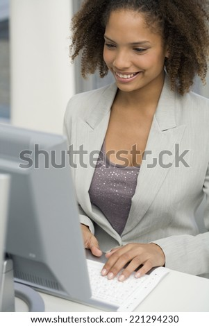African businesswoman typing on computer - stock photo