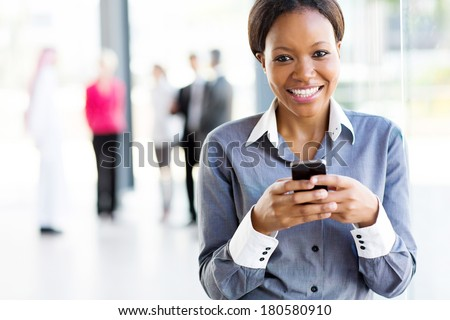 african businesswoman using smart phone in modern office - stock photo