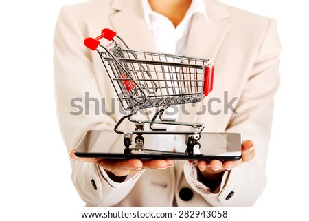African businesswoman with shopping cart and tablet. - stock photo