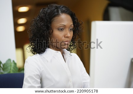 African businesswoman working at desk - stock photo