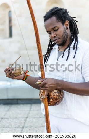African Capoeira Rastaman,playing a instrument berimbau - stock photo