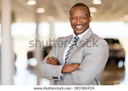 african car sales consultant with arms folded in showroom - stock photo