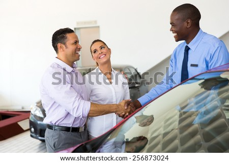 african car salesman handshaking with happy couple
