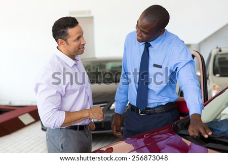african car salesman selling a car to mid age customer in showroom - stock photo