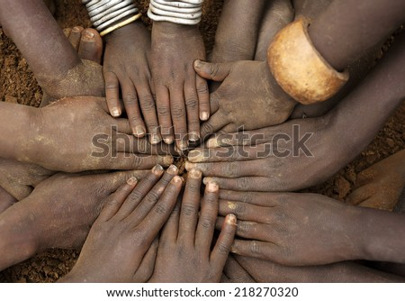 African ceremony of the Mursi tribe, close-up of hands of a group of children, Ethiopia - stock photo