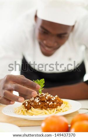 african chef garnishing spaghetti in kitchen - stock photo