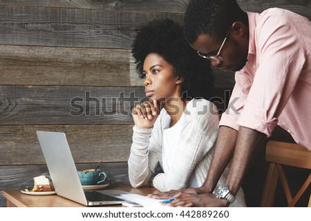 African colleagues working together on a project, facing a dead end situation, trying to come to a compromise: woman looking into distance while man standing behind her leaning his hands on the table - stock photo