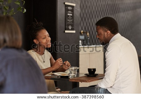 African couple enjoying coffee date in a modern cafe - stock photo