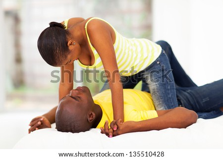 african couple flirting in bed - stock photo