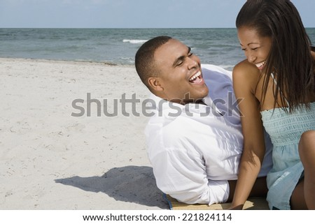 African couple laughing at beach - stock photo
