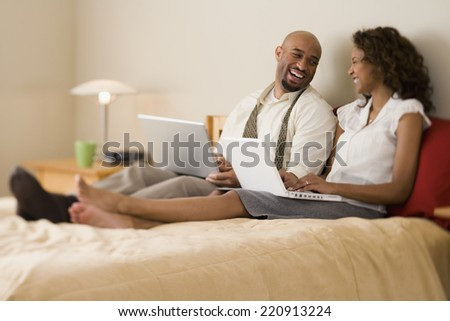 African couple laughing in bed - stock photo