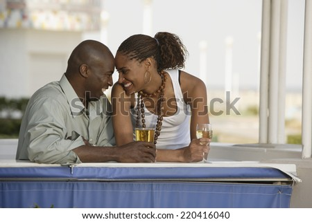 African couple smiling at each other with cocktails - stock photo