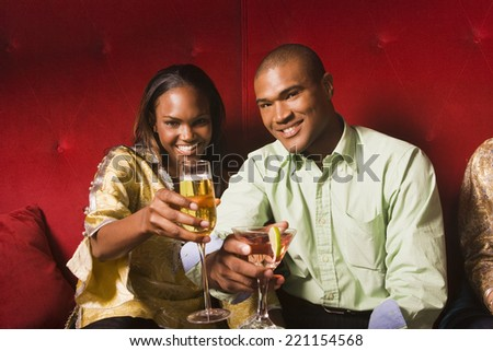 African couple toasting with cocktails - stock photo