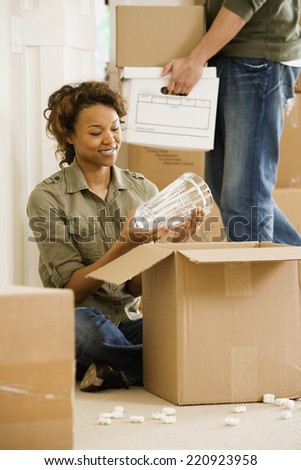 African couple unpacking in new house - stock photo