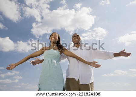 African couple with arms outstretched - stock photo