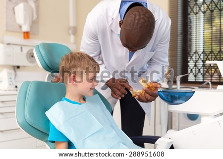 african dentist explaining the dental procedure to little boy - stock photo