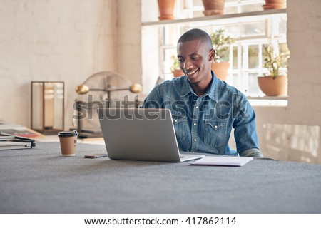 African designer working on laptop in his beautifully lit studio - stock photo