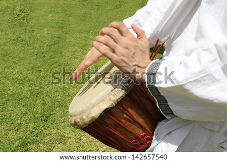 african djembe drummer, green grass background - stock photo