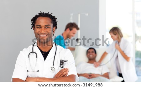 African doctor smiling at the camera with team in the backgroud