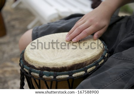 African Drum with a hand on a skin of the drumhead. An Instrument for Percussionists and Musicians. - stock photo