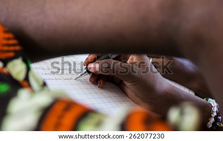 African Education Symbol: Writing A Letter. A young African girl writes down a letter to a friend of hers with a black pen. - stock photo