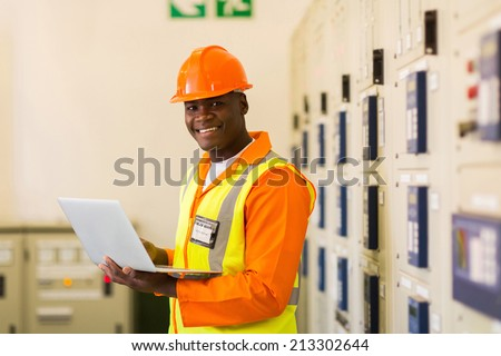african electrical engineer using laptop computer in power plant control room - stock photo
