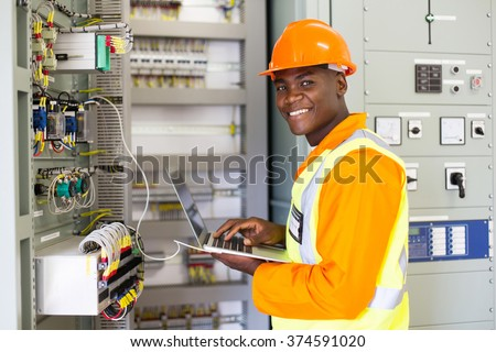 african electrical worker using laptop computer checking transformer - stock photo