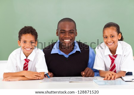 african elementary school teacher and students in classroom - stock photo